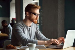 Focused millennial redhead man using laptop