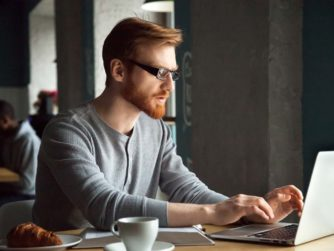 Focused millennial redhead man using laptop